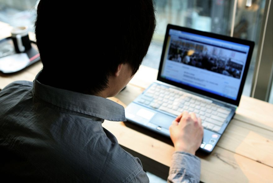 """A man who goes by the Internet alias """"Forest Intelligence"""" looks at the """"Jasmine Movement"""" website at a cafe in Seoul. He oversees the recruitment of volunteers and maintains the website. (Associated Press)"""