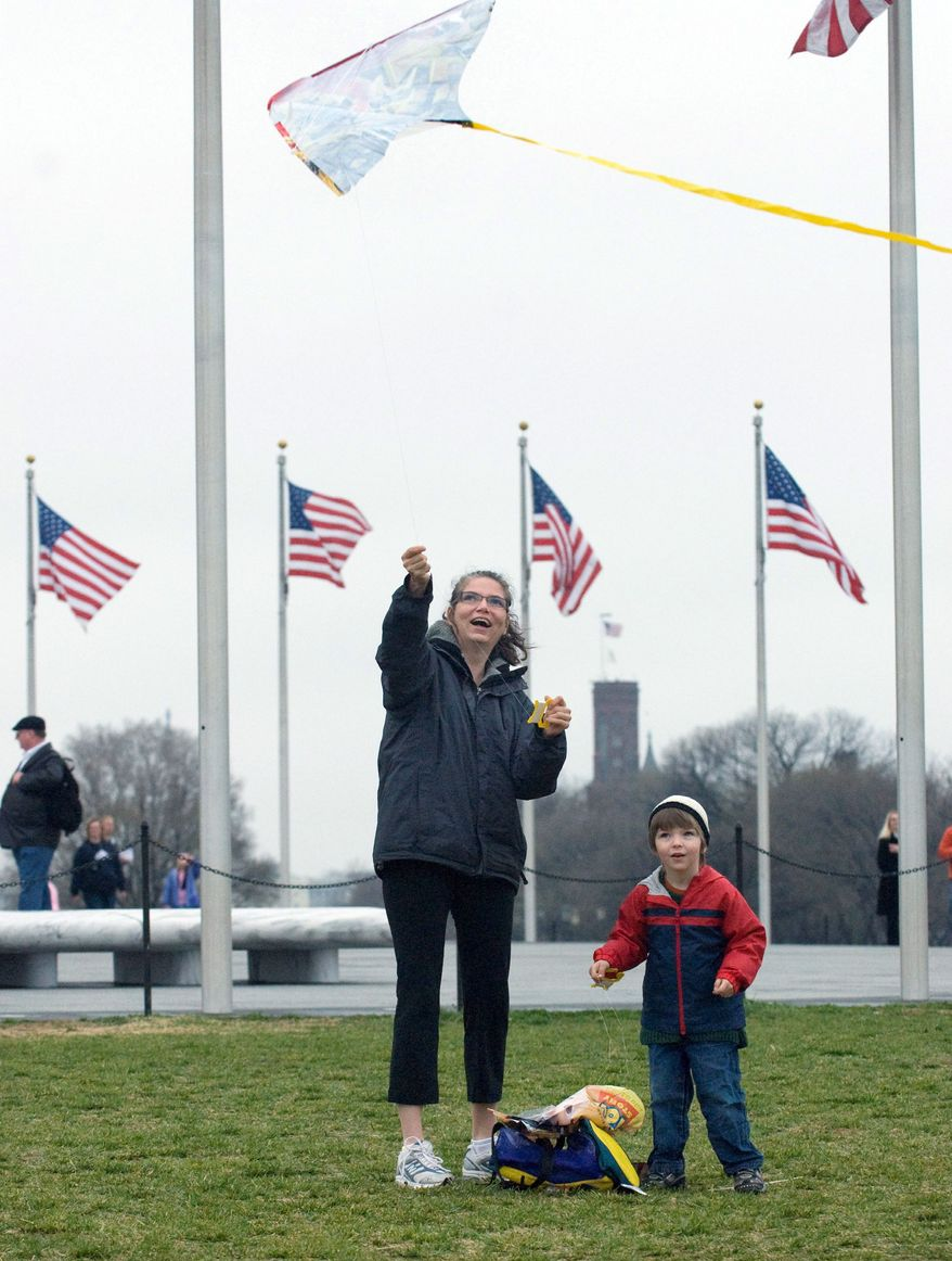 Gabrielle Davison of Bowie and her son Dominic try to get their kite airborne during the 2009 Kite Festival, then sponsored by the Smithsonian, on the grounds of the Washington Monument. (J.M. Eddins Jr./The Washington Times)