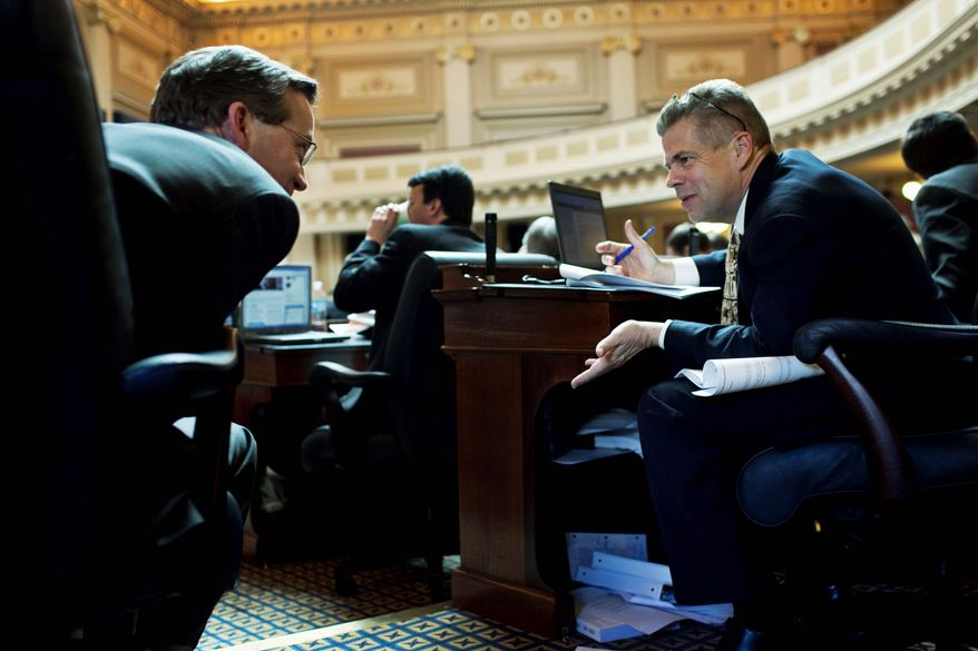 Republican House Majority Leader M. Kirkland Cox (right) talks with fellow Republican Delegate S. Chris Jones, Chesapeake-Suffolk (left), during debate on Gov. Robert F. McDonnell's budget amendments on the House floor at the Capitol on Wednesday. (Drew Angerer/The Washington Times)