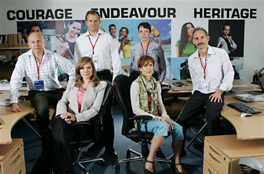 """In this Tuesday March 29, 2011 photo released  by the BBC in London,  cast members of the Olympic satire show """"Twenty-Twelve"""" are seen. From Left: Vincent Franklin (NICK), Jessica Hynes (SIOBHAN), Hugh Bonneville (IAN), Olivia Colman (SALLY), Amelia Bullmore (KAY), Karl Theobald (GRAHAM).  In the mock-documentary format pioneered by comedies like """"The Office,"""" the show goes behind the scenes at the fictional Olympic Deliverance Commission, run by long-suffering """"Head of Deliverance"""" Ian Fletcher (Hugh Bonneville, recently seen as aristocratic Lord Grantham in costume drama """"Downton Abbey"""").  (AP Photo- Jack Barnes /HO BBC) EDITORIAL USE ONLY NO SALES   UK OUT TV OUT MANDATORY CREDIT BBC"""