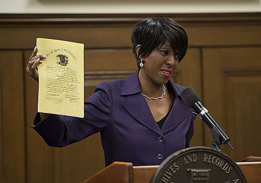 "Cheryl Wills, a TV journalist and author of the book ""Die Free,"" holds up a copy of the discharge record she found for her great-great-great-grandfather Sandy Wills, who served from 1863 to 1865 in the Union Army. Ms. Wills was on hand at the National Archives in Washington on Wednesday, April 6, 2011, as the archives announced that Civil War documents now will be made available online at Ancestry.com. (Barbara L. Salisbury/The Washington Times)"