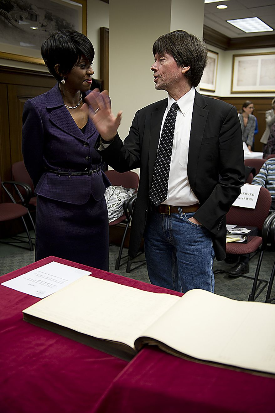 Documentary filmmaker Ken Burns (right) talks with TV journalist and author Cheryl Wills following an announcement on Wednesday, April 6, 2011, at the National Archives in Washington that Civil War documents will now be available online outside the archives. The document seen here lists draft registrations for the war. (Barbara L. Salisbury/The Washington Times)