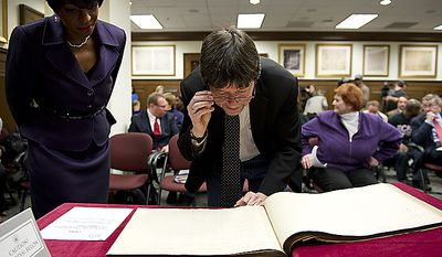 Documentary filmmaker Ken Burns (right) and TV journalist and author Cheryl Wills look at a book that contains Civil War draft registration records at the National Archives in Washington on Wednesday, April 6, 2011, following the announcement that Civil War records such as these will now be available online at Ancestry.com. (Barbara L. Salisbury/The Washington Times)