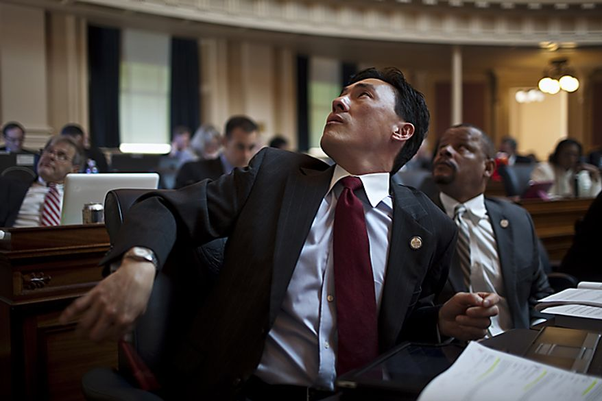 Democratic Delegates Mark Keam, left, and Luke Torian, right, react to the scoreboard of votes on governor's budget amendments, on the House floor at the Capitol, in Richmond, Wednesday, April 6, 2011. (Drew Angerer/The Washington Times)