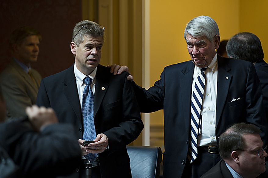 Del. Lacey Putney, R-Bedford, puts his hand on Republican Majority Leader Kirkland Cox's shoulder after the House passed the Republican sponsored state redistricting plan, during a House session at the Capitol, in Richmond, Va., Tuesday, April 5, 2011. (Drew Angerer/The Washington Times)