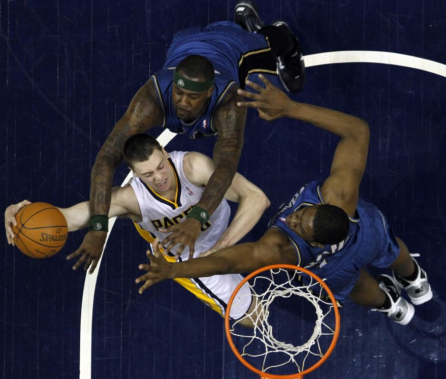 Indiana Pacers forward Tyler Hansbrough , center, is intentionally fouled by Washington Wizards forward Andray Blatche, top,while shooting over Wizards' Kevin Seraphin in the third quarter of an NBA basketball game in Indianapolis, Wednesday, April 6, 2011. (AP Photo/Michael Conroy)