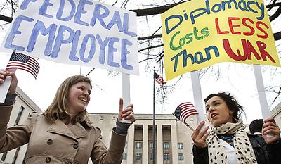 Susanne Brands, 22, left, and Mina Seljogi, 21, both interns at the American Foreign Service Association, attend a rally of U.S. diplomats and federal workers against the prospect of a government shutdown, Friday, April 8, 2011, in Washington. (AP Photo/Jacquelyn Martin)
