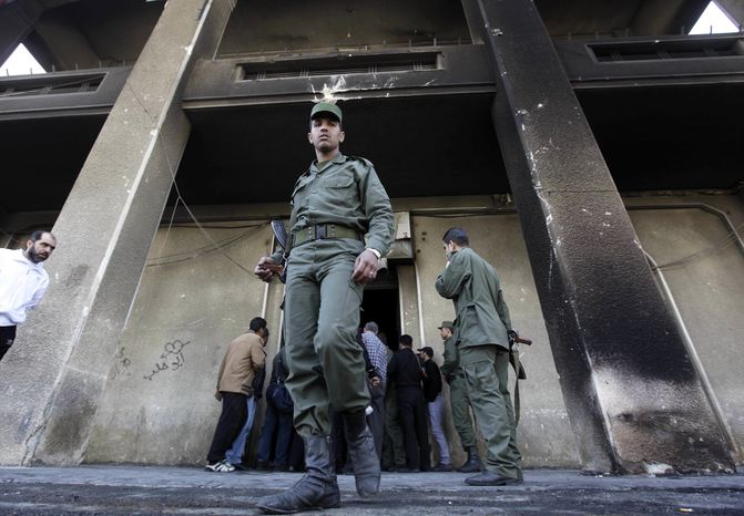 ** FILE ** In this March 21, 2011, photo, Syrian army soldier steps out from the burned court building that was set on fire by Syrian anti-government protesters, in the southern city of Daraa, Syria. (AP Photo/Hussein Malla)