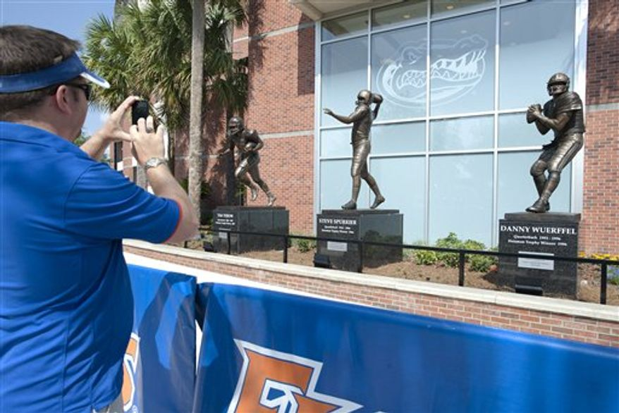 A fan shoots a photo of statues of Florida's three Heisman Trophy winners that were unveiled at halftime during the Orange and Blue spring football game in Gainesville, Fla., Saturday, April 9, 2011. The statues are of, from left, Tim Tebow, Steve Spurrier and Danny Wuerffel. (AP Photo/Phil Sandlin)