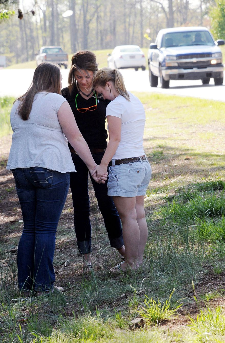 From left, Jordan Crowe, Raegan Fulmer and Natalie White pray on Friday near a stretch of Highway 129 in Duncan, S.C., where Aaron Shawn Hill, 18, died in a car crash. The teenager was killed in a wreck on a stretch of highway named in memory of his father, a soldier slain in Afghanistan. (Associated Press)
