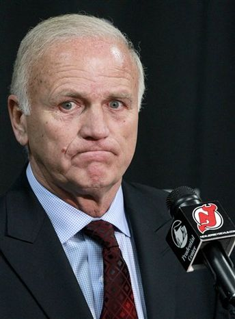 New Jersey Devils head coach Jacques Lemaire reacts while answering a question about what his wife thought of his possible retirement as he announced his departure at the end of an NHL hockey game against the Boston Bruins, April 10, 2011, in Newark, N.J. The Devils won 3-2. (AP Photo/Julio Cortez)