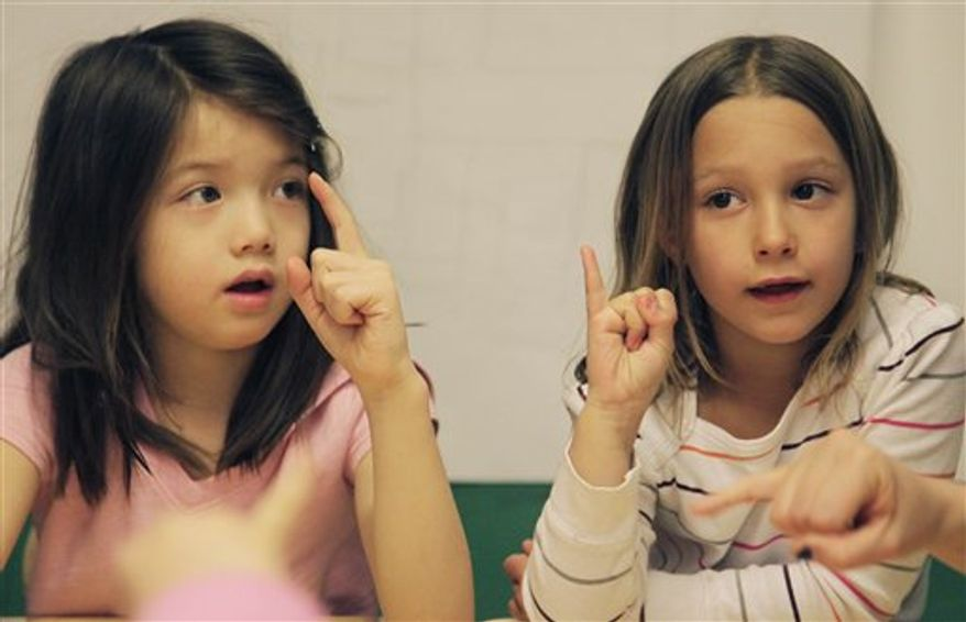 In this March 31, 2011 photo, first-graders learn sign language at the Blue School in New York. The private preschool and elementary school was founded by original members of the Blue Man Group so they could send their own children to a school that was creative enough for them.  (AP Photo/Mark Lennihan)