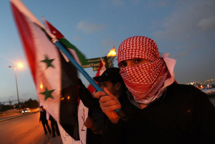 A Syrian protester holds the national flag in front of the Syrian Embassy in Amman, Jordan, on Saturday, April 9, 2011, during a vigil calling for President Bashar Assad to step down. (AP Photo/Nader Daoud)
