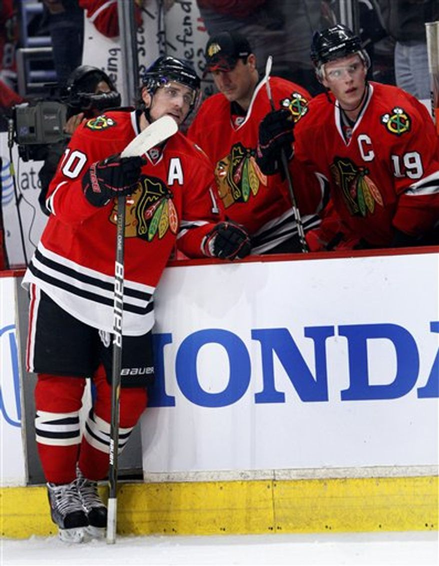 From left to right, Chicago Blackhawks' Michael Frolik, Bryan Bickell and Ben Smith react after the Detroit Red Wings defeated them 4-3 in the last game of the NHL regular season on Sunday, April 10, 2011. (AP Photo/Charles Cherney)