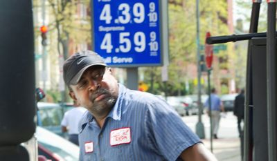"""Dane Ellis, a full-service attendant at the Exxon station at the corner of 4th Street and Pennsylvania Avenue in Southeast, pumps gas into a truck on Monday. Station manager David """"Woody"""" Woodall said that sales volume hasn't dropped off. """"We have a lot of regular customers that just need their gas, so they're going to come here every day anyway,"""" he said. (Barbara L. Salisbury/The Washington Times)"""