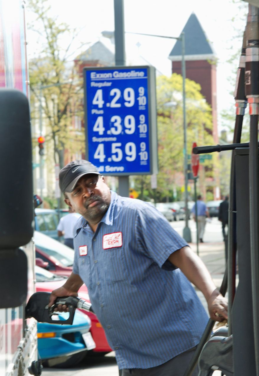 "Dane Ellis, a full-service attendant at the Exxon station at the corner of 4th Street and Pennsylvania Avenue in Southeast, pumps gas into a truck on Monday. Station manager David ""Woody"" Woodall said that sales volume hasn't dropped off. ""We have a lot of regular customers that just need their gas, so they're going to come here every day anyway,"" he said. (Barbara L. Salisbury/The Washington Times)"