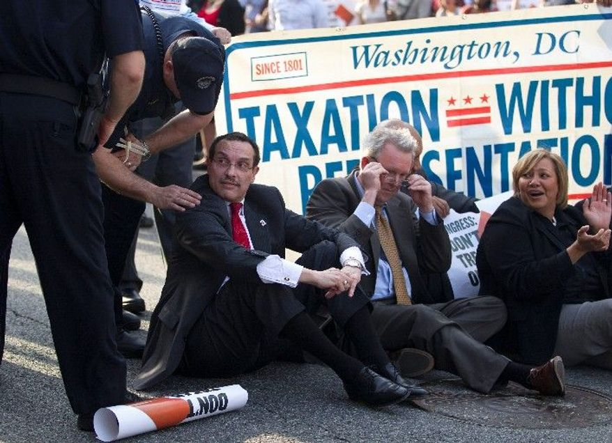 """ASSOCIATED PRESS A Capitol Police officer talks to D.C. Mayor Vincent C. Gray before he was arrested Monday for """"impeding traffic"""" during a protest on Capitol Hill of the restrictions placed on the District as part of the federal budget deal. """"D.C. deserves to be free,"""" Mr. Gray said."""