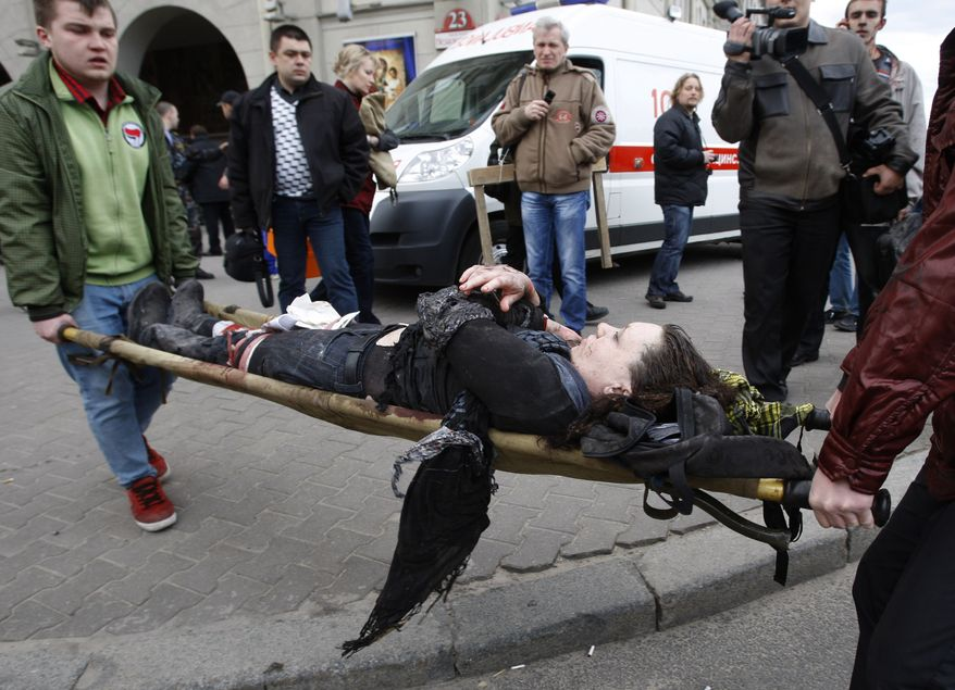 Rescuers carry a wounded person to an ambulance in Minsk, Belarus, on Monday, April 11, 2011, after an explosion tore through a main subway station in the Belarusian capital during the evening rush hour. (AP Photo/Sergei Grits)