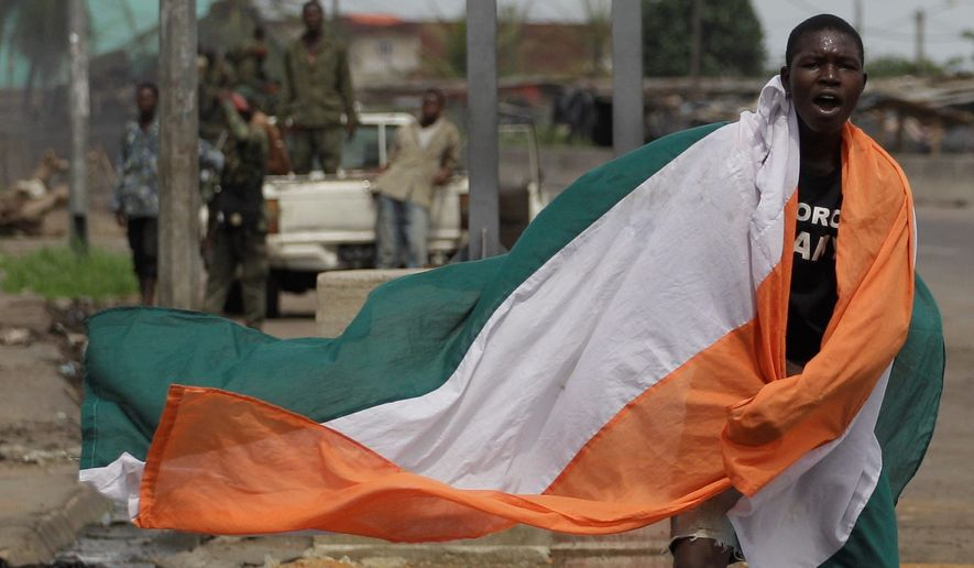 An Ivory Coast resident wears his country's flag as he celebrates the arrest of Laurent Gbagbo. The strongman had refused to concede power after losing November's presidential election to Alassane Ouattara. (Associated Press)