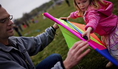 """Joe Kleeman (left) helps Hada Carson, 4, a family friend, prepare her kite for flight during the Blossom Kite Festival on the National Mall in Washington on Sunday, April 10, 2011. Mr. Kleeman said he hadn't been worried about a possible government shutdown ruining their day. """"Once you tell all the kids you're going to fly kites, you're still going to go, no matter what the government does. We'd be out here either way."""" (Drew Angerer/The Washington Times)"""