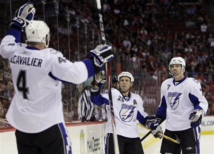 Carolina Hurricanes' Erik Cole (26) and Tampa Bay Lightning's Martin St. Louis struggle for possession of the puck during the third period of an NHL hockey game in Raleigh, N.C., Saturday, April 9, 2011. Tampa Bay won 6-2. (AP Photo/Gerry Broome)
