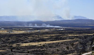 Uncontrolled wildfires burn near Fort Davis, Texas, on Sunday, April 10, 2011. A fast-moving wildfire spread to more than 60,000 acres in Presidio and Jeff Davis counties, where it destroyed about 20 homes in Fort Davis. (AP Photo/Billy Marginot)