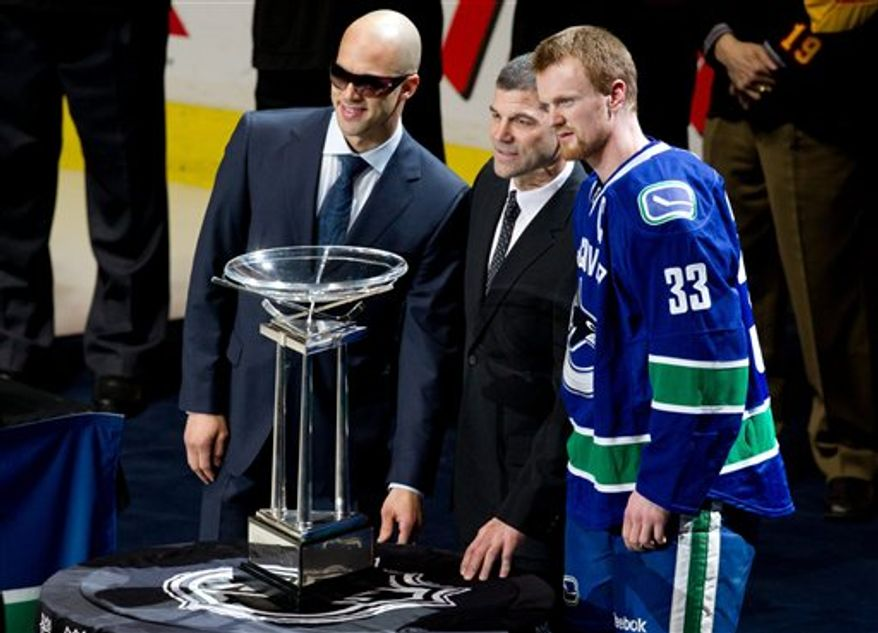 Vancouver Canucks' captain Henrik Sedin, right, of Sweden, and injured teammate and alternate captain Manny Malhotra, left, stand with NHL Senior VP of Hockey Operations Kris King after they received the President's Trophy prior to an NHL hockey game against the Minnesota Wild in Vancouver, British Columbia on Thursday April 7, 2011. The trophy is awarded to the team that finishes in first place overall in the league. Malhotra underwent eye surgery after he was hit by a puck in March. (AP Photo/The Canadian Press, Darryl Dyck)