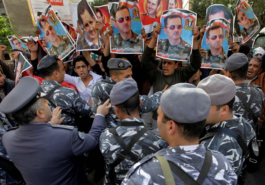 Supporters of Syrian President Bashar Assad raise posters depicting the leader as they protest against pro-reform activists. Pro-government gunmen attacked two villages in a move to crush the uprising against Mr. Assad's regime, witnesses said. (Associated Press)