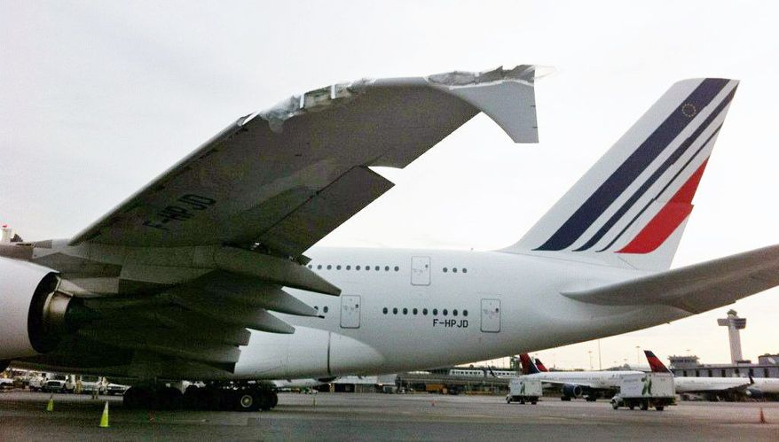 A damaged Air France Airbus A380 sits at John F. Kennedy International Airport in New York on Tuesday. The world's largest passenger aircraft clipped a much smaller regional jet while taxiing on a dark, wet runway on Monday. (Associated Press)