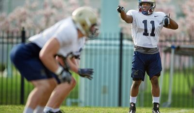 Drew Angerer/The Washington Times Cornerback Kwesi Mitchell (11) directs the defensive backfield Monday during practice at the Naval Academy in Annapolis. However the defensive backfield takes shape, it will take its cues from Mitchell.