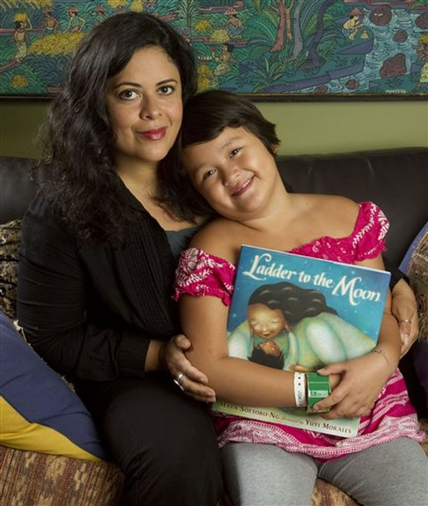 """This Tuesday, March 29, 2011 photo shows Maya Soetoro-Ng, left, and her daughter Suhaila Ng, 6, as they look at Soetoro-Ng's new book, """"Ladder to the Moon,"""" at their home in Honolulu. Soetoro-Ng, President Obama's sister, draws on memories of their mother, Ann Dunham, for her new picture book.   (AP Photo/Eugene Tanner)"""