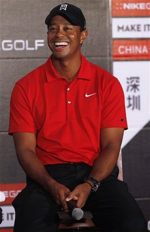 U.S. golfer Tiger Woods smiles during a news conference as part of his Asian tour in Mission Hill Dongguan club house in Dongguan, southern China's Guangdong province, Tuesday, April 12, 2011.  Woods will visit Beijing and Seoul in South Korea during the tour. (AP Photo/Kin Cheung)