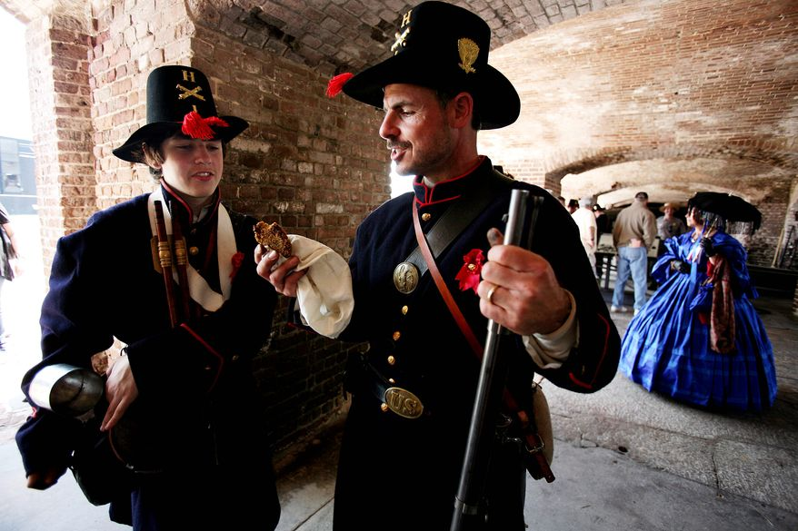 Jacob Borror (left) shares a grit cake with his father, Matt Borror, as they portray U.S. Army soldiers guarding Fort Sumter on Monday, April 11, 2011, in Charleston, S.C. (AP Photo/The Post and Courier, Grace Beahm)