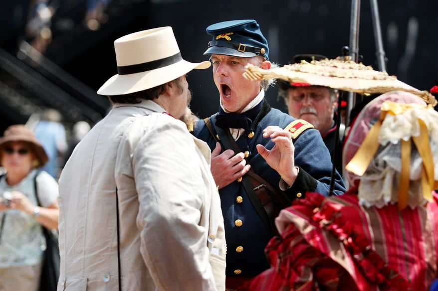 Hours from the re-creation of the bombardment of Fort Sumter, re-enactors' tensions run high as Mark Silas Tackitt of Seattle, who plays Maj. Robert Anderson, commander of Fort Sumter, has fort visitor Major Heros Von Borcke, who is dressed as Confederate sympathizer, tossed from the fort -- at musketpoint -- until he removed a Jefferson Davis button from his lapel, on Monday, April 11, 2011, in Charleston, S.C. (AP Photo/The Post and Courier, Grace Beahm)