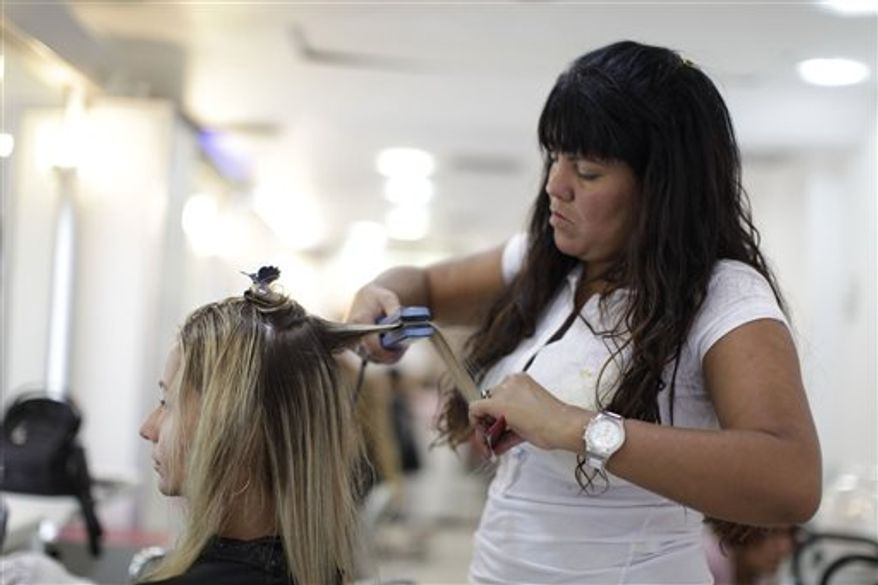 FILE - This Feb. 3, 2011 file photo shows Adriana Guedes as she has her hair straightened by hair dresser Tania Machado at a salon in Ipanema, Rio de Janeiro, Brazil. The Brazilian Blowout surfaced around 2005 in Brazil, where a combination of high humidity and a largely mixed-race, curly haired population made for a nation of eager customers. It soon spread throughout North America and Europe. (AP Photo/Felipe Dana, File)