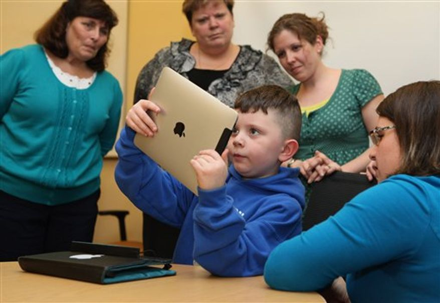 Kindergarten teacher Sue larue, tries out an iPad Tuesday, April 12, 2011 in Auburn, Maine. Five kindergarten teachers were given iPads to try out in preparation for next year when nearly 300 kindergarteners will be given their own iPad2s.  (AP Photo/Joel Page)