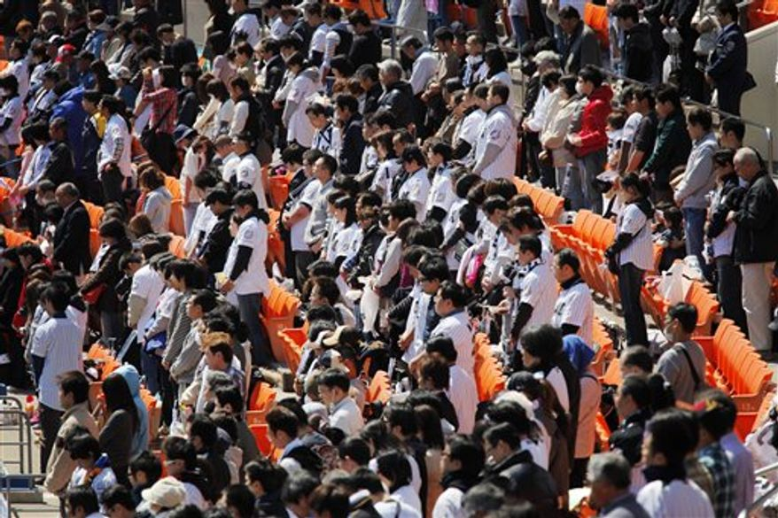 Baseball fans observe a moment of silence for the victims of the March 11 earthquake and tsunami before the start of a game between the Rakuten Golden Eagles, a Japanese professional team based in Sendai, northeastern Japan, and the Lotte Marines in Chiba, near Tokyo, on Tuesday, April 12, 2011.  The 2011 pro baseball regular season kicked off on Tuesday in Japan. (AP Photo/Itsuo Inouye)