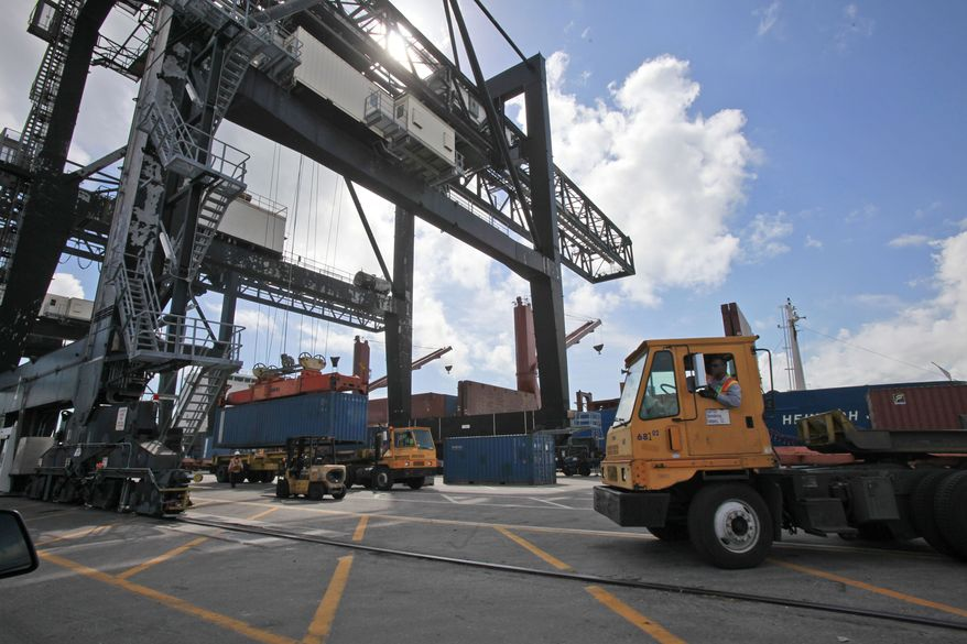 Large cranes load shipping containers onto trucks at the Port of Miami on Feb. 4, 2011, in Miami. U.S. companies sold fewer products overseas in February, but the trade deficit still narrowed because of a big decline in oil imports. (AP Photo/Wilfredo Lee)
