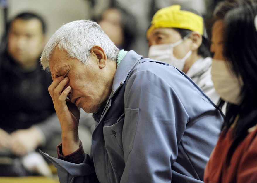 Residents of Iitate village listen Wednesday to their mayor explain a government plan to evacuate residents from the village that is about 24 miles from the radiation-spewing Fukushima Dai-ichi nuclear plant in northeastern Japan. (Kyodo News via Associated Press)
