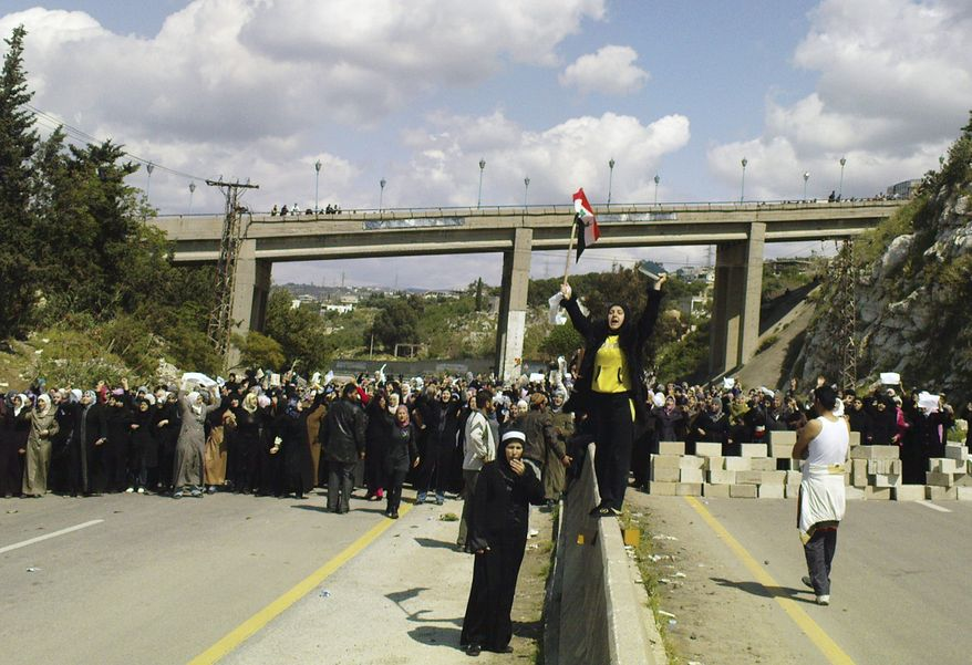 Thousands of Syrian women and children holding white flags and olive branches blocked a main coastal highway in Banias, Syria, on Wednesday, April 13, 2011, to demand that authorities release those detained in a crackdown on opponents of the Assad regime, witnesses said. (AP Photo)