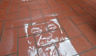 "Detained Chinese artist Ai Weiwei's likeness is sprayed on a Hong Kong sidewalk with the words, ""Who's afraid of Ai Weiwei?"" The social activist was taken into police custody April 3 and is being investigated for allegedly evading his taxes, a Hong Kong newspaper reported. (Associated Press)"
