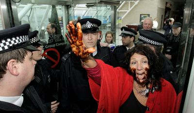 "Diane Wilson, a fourth-generation Texas fisherwoman, her face smeared with syrup to represent oil, protests against BP as British police officers prevent her from entering the London conference center where the petroleum giant held the annual general meeting of its shareholders Thursday. ""I think a lot of the shrimpers are concerned,"" she said. (Associated Press)"