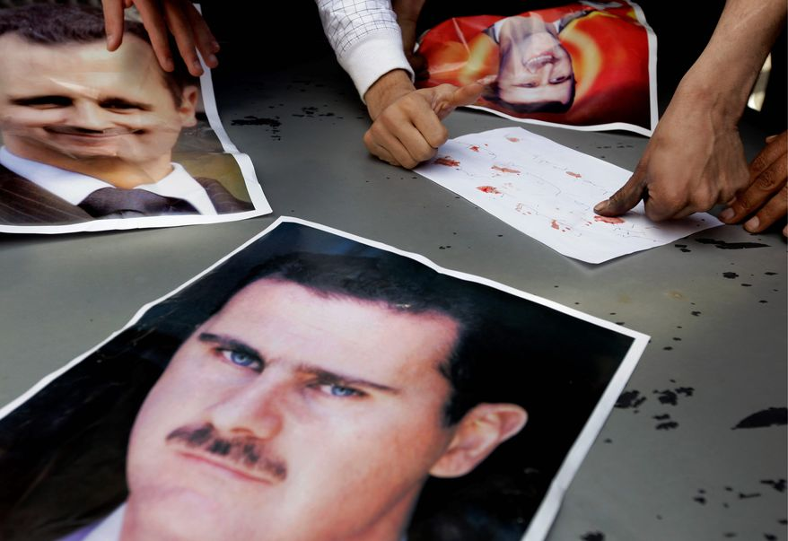 Supporters of Syrian President Bashar Assad stamp their fingerprints in their blood next to posters depicting him in a show of support, as they protest reformists in front the Syrian Embassy in Beirut this week. The opposition to Mr. Assad's rule is seeking a stronger U.S. diplomatic response. (Associated Press)