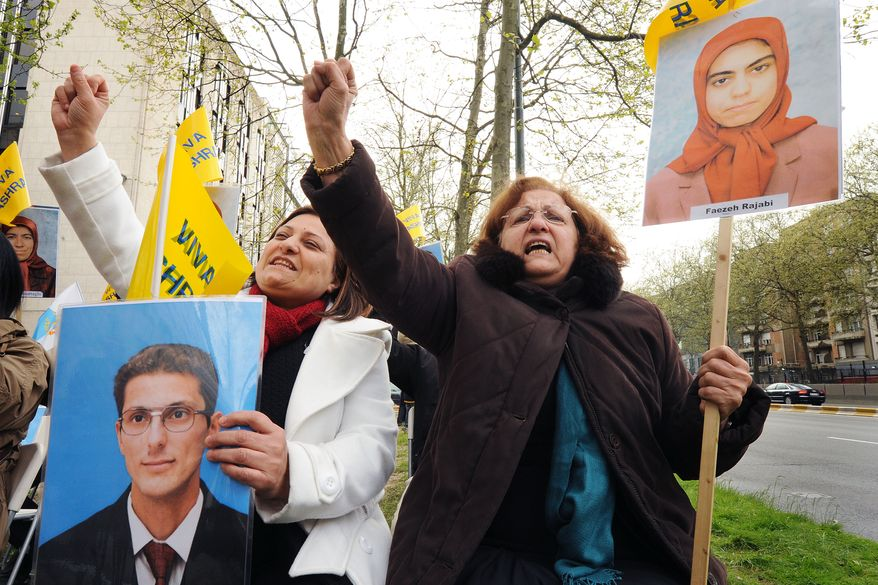 Family members and friends of killed Camp Ashraf residents hold pictures of the deceased as they scream slogans while protesting in front of the U.S. Embassy in Brussels on Thursday, April 14, 2011. On Friday, April 8, 2011, the Iraqi army launched a military raid on the camp that left a number of dead and injured. (AP Photo/Geert Vanden Wijngaert)
