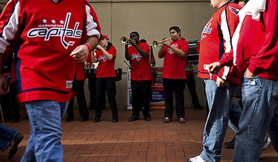 Fans in Caps uniforms walk in front of the Verizon Center as the pep band from Freedom High School in Woodbridge, Va., plays before a playoff game between the Washington Capitals and the New York Rangers in Washington on Wednesday, April 13, 2011. (Drew Angerer/The Washington Times)