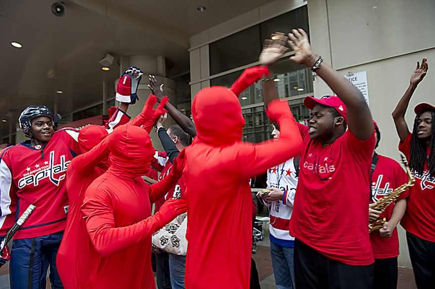 "Eric Mitchell (left) and ""The Red Men"" high-five Washington Capitals fans outside the Verizon Center before the playoff game on Wednesday, April 13, 2011, in Washington. (Barbara L. Salisbury/The Washington Times)"