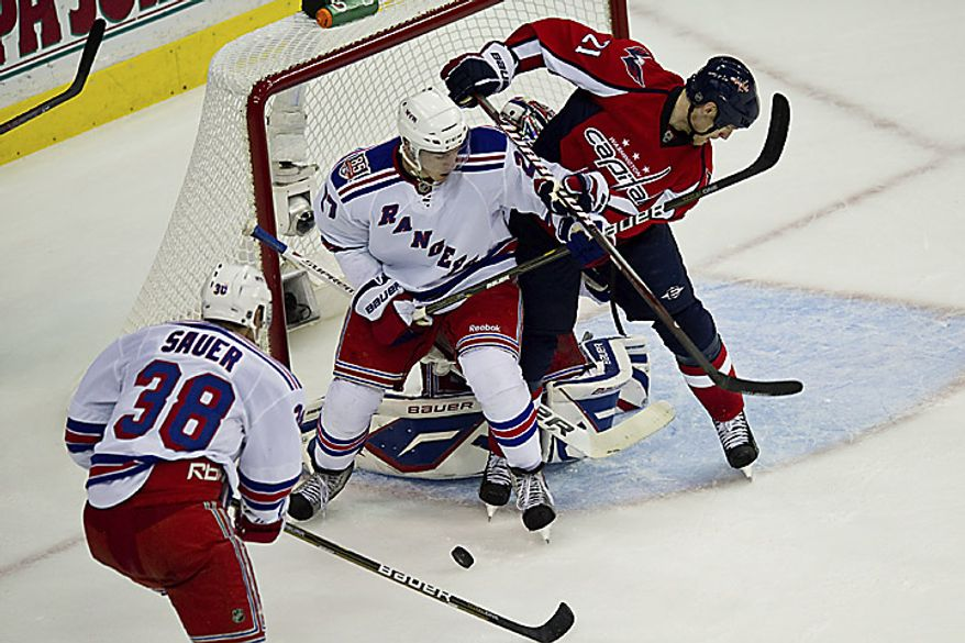 Capitals center Brooks Laich fights for the puck near the Rangers' goal during the NHL playoff game at the Verizon Center in Washington on Wednesday, April 13, 2011. (Drew Angerer/The Washington Times)