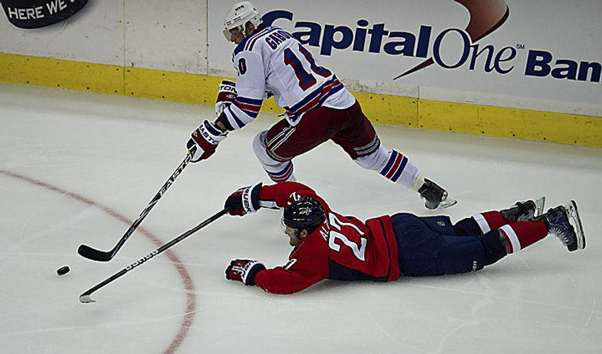 Capitals defenseman Karl Alzner dives for the puck against Rangers forward Marian Gaborik during the second period of a playoff game at the Verizon Center in Washington on Wednesday, April 13, 2011. (Drew Angerer/The Washington Times)
