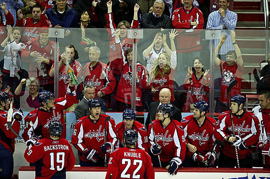 Fans and the Washington Capitals bench react in excitement after Alex Ovechkin's goal was confirmed by the referees to even the score at 1-1 during the third period of a playoff game against the New York Rangers at the Verizon Center in Washington on Wednesday, April 13, 2011. (Drew Angerer/The Washington Times)