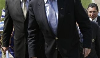 FIFA President Joseph S. Blatter, center, walks with El Salvador's Soccer Federation President Carlos Mendez, left, as they arrive to El Salvador's Soccer Federation headquarters in San Salvador, El Salvador, Wednesday April 13 , 2011.  (AP Photo/Luis Romero)